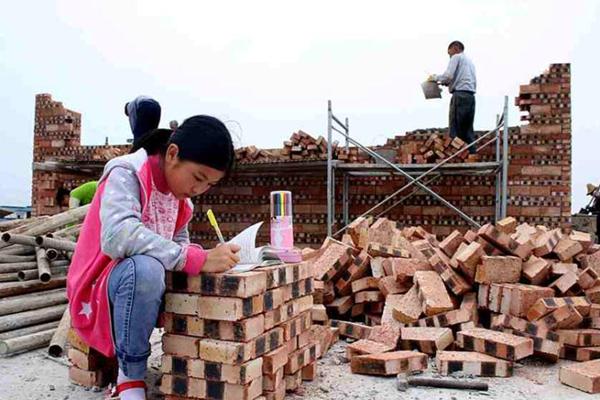 垒起砖头当书桌 11岁女孩工地上学习
