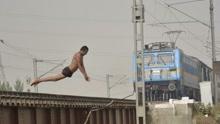 印度男孩爬火车跳恒河 展特技