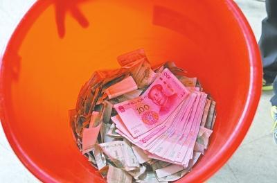 真·土豪?男子投数十张百元大钞在公交投币箱
