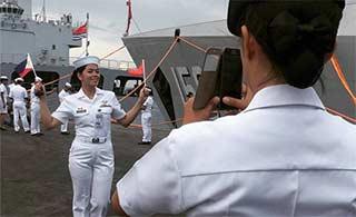 菲女兵拿中菲国旗军舰前留影