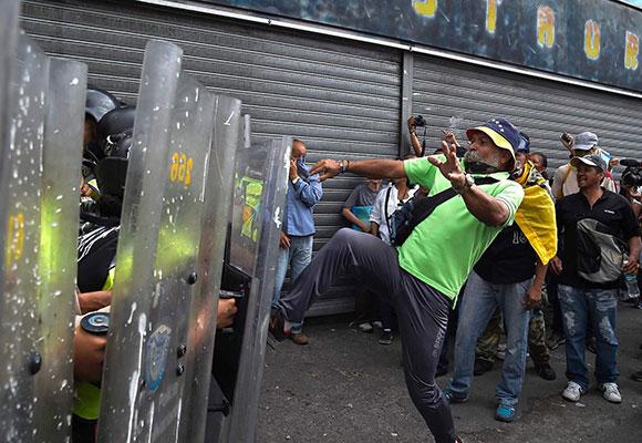 委内瑞拉货币贬值达99.5% 民众脚踹警察