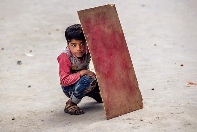 环球图片一周精选 小男孩藏木板后躲避冲突