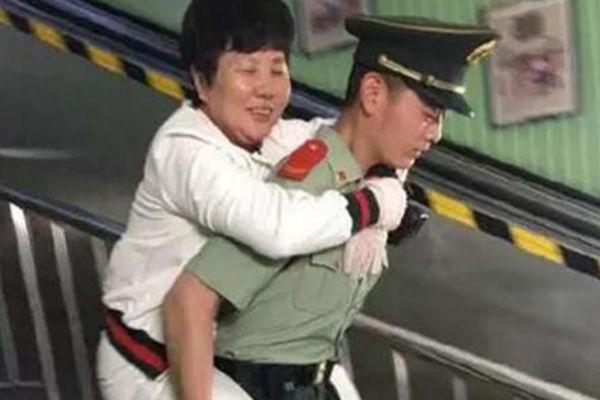 北京地铁内暖心一幕:军人背大妈下楼梯