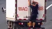 """货车错过高速出口 胖哥用""""人体""""遮挡号牌倒车"""