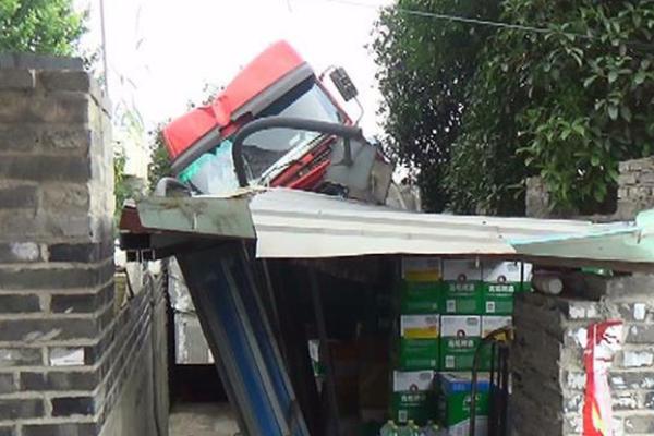货车为避让轿车 撞断路灯冲上仓库顶