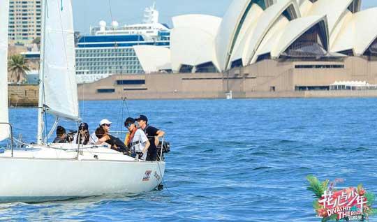 """体验过南美洲的风情万种和非洲的自然原生态后,""""花少团""""抵达四面环海的澳洲,开启缤纷清凉的澳大利亚夏日初体验。首站,他们来到环境优美、气候宜人的海滨城市悉尼。这里是世界著名近海帆船赛事举办地,吸引着众多帆船兴趣者前来参观感受。此次""""花少团""""也将奔赴帆船学校,体验一场终身难忘的帆船自驾行。   """"花少团""""对帆船驾驶表现出了不小的兴趣,尤其教练员中还有颜值颇高的澳洲小哥哥,宋祖儿更是喜不自禁。登船前,穿戴专业设备及学习救生知识必不可少"""