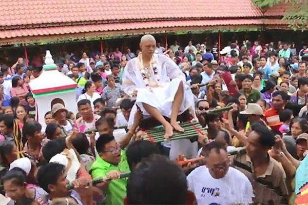 泰国某镇长儿子出家 向民众撒万元钞票