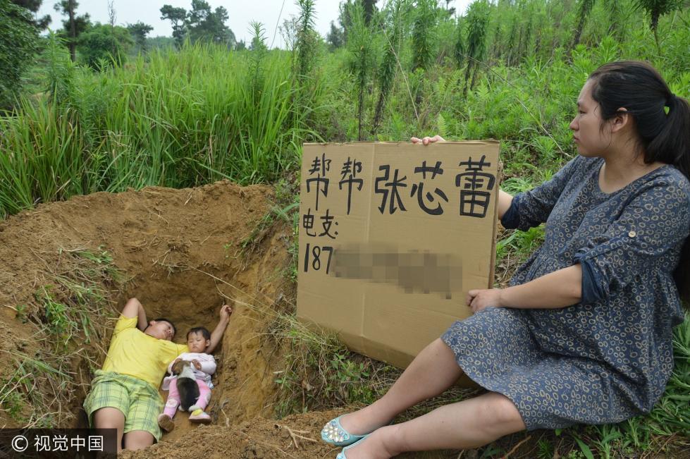 """2017年6月23日,四川内江,父亲张利勇在一块自留地内,为患地中海贫血症的2岁女儿挖了一个""""坟墓"""",带着女儿躺入其中。"""