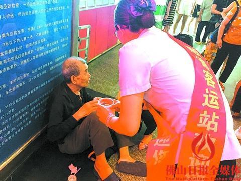 中国侨网工作人员在旁边照料老人。(区嘉燕 摄)