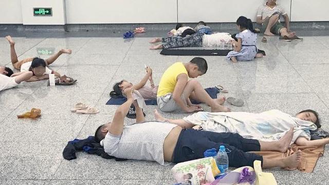 """杭州地铁站""""纳凉族""""扎堆 直接躺地上睡"""