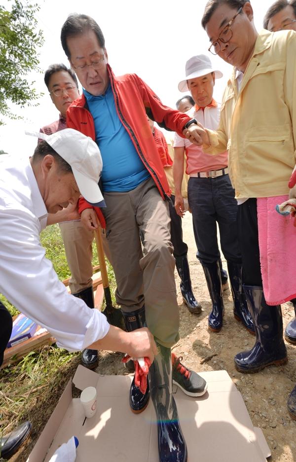 韩在野党党首赴灾区穿雨靴照惹争议:像国王在大臣帮助下穿鞋