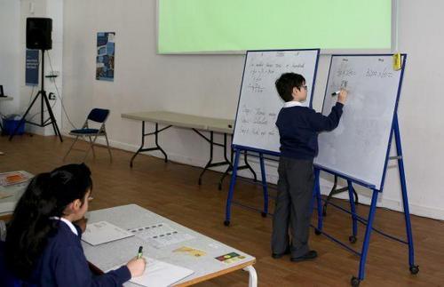 """中国侨网资料图片:""""九九乘法表""""走进英国小学课堂。在英国伦敦东北部埃塞克斯郡的哈里斯小学,一名三年级(相当于国内二年级)的小学生在白板上用竖式计算。 新华社记者韩岩摄"""