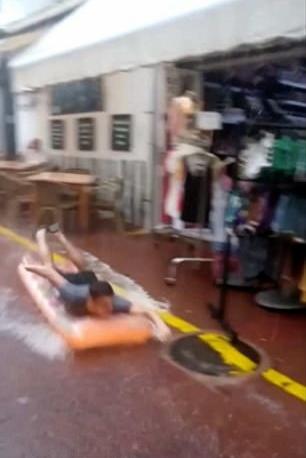 真会玩!男孩暴雨趴气垫将湿滑街道当滑梯