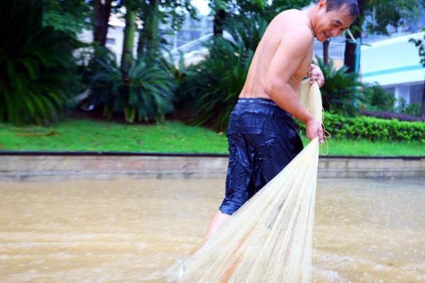 雨水冲击广西河流水位上涨 民众雨中网鱼