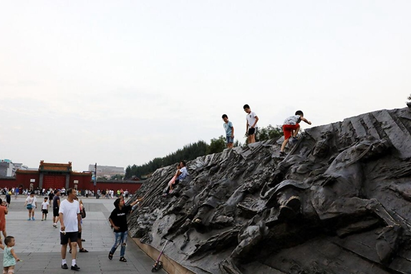 沈阳故宫浮雕成攀爬墙 攀爬者以儿童居多