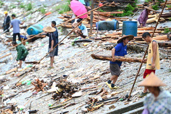 发洪水财?广西村民在泄洪口冒险打捞木材