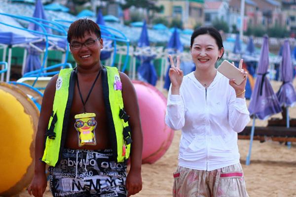 """海边浴场工作者与游客的合照 30天晒成""""黑人"""""""