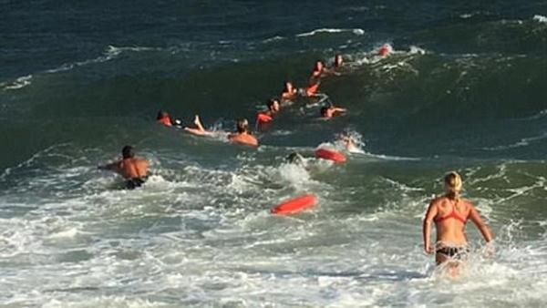齐心协力 美救生员组成人链合力救出海中被困者