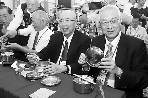 """图片说明:吴敦义(右)20日中午跟参会人士一起吃""""党徽便当""""。"""
