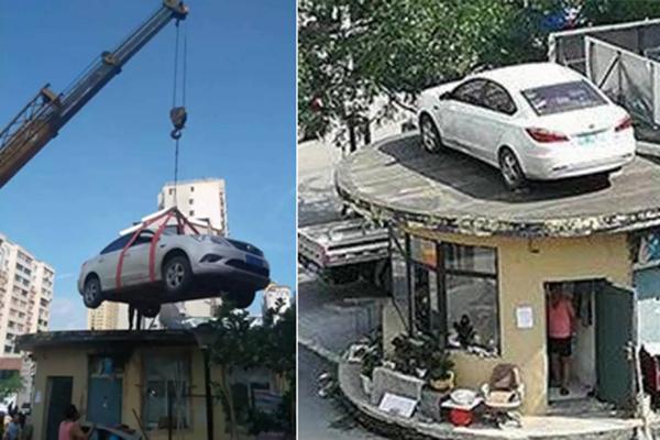 辽宁一女子用轿车堵小区门 车被吊上房顶