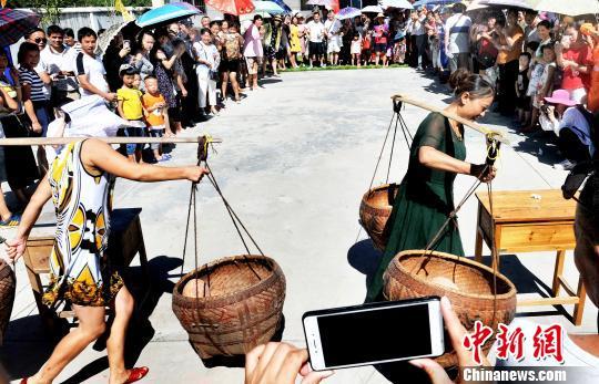 江西德兴乡村挑南瓜比赛 男女同场比拼游客踊跃参与