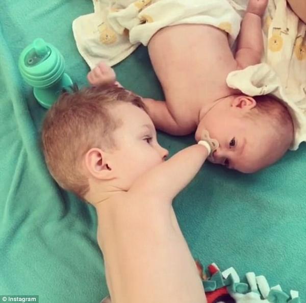 美残疾男童用残肢给弟弟喂奶嘴 画面暖心