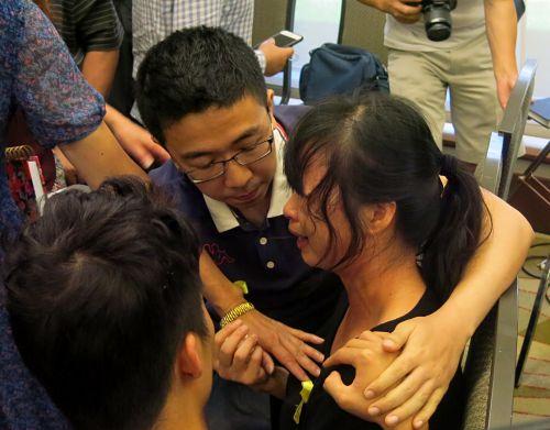 章莹颖(右)母亲痛哭,章莹颖弟弟(左)与男友(中)在旁安慰。(美国侨报网)