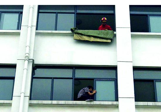 聋哑学生坐5楼窗台欲跳楼 消防员飞身一跃将其推回屋