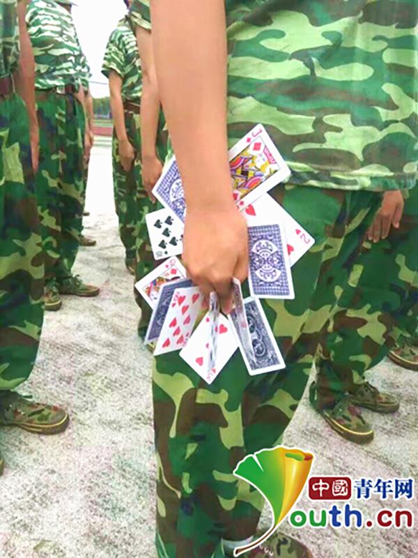 高校军训让新生手夹十余张扑克牌立军姿,教官:是传统