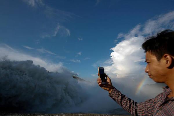 越南水电站开闸泄洪 民众大坝上淡定自拍