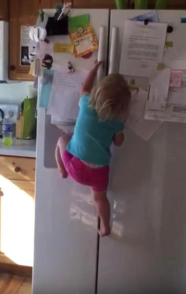 美两岁女童徒手爬冰箱顶展现惊人臂力
