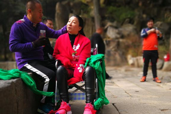 男子背瘫痪妻子8小时爬上泰山 恩爱18年