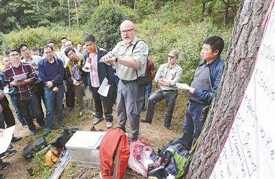 中国侨网德国专家现场讲解演示近自然林经营及目标树单株抚育方法。(记者 徐能 摄)