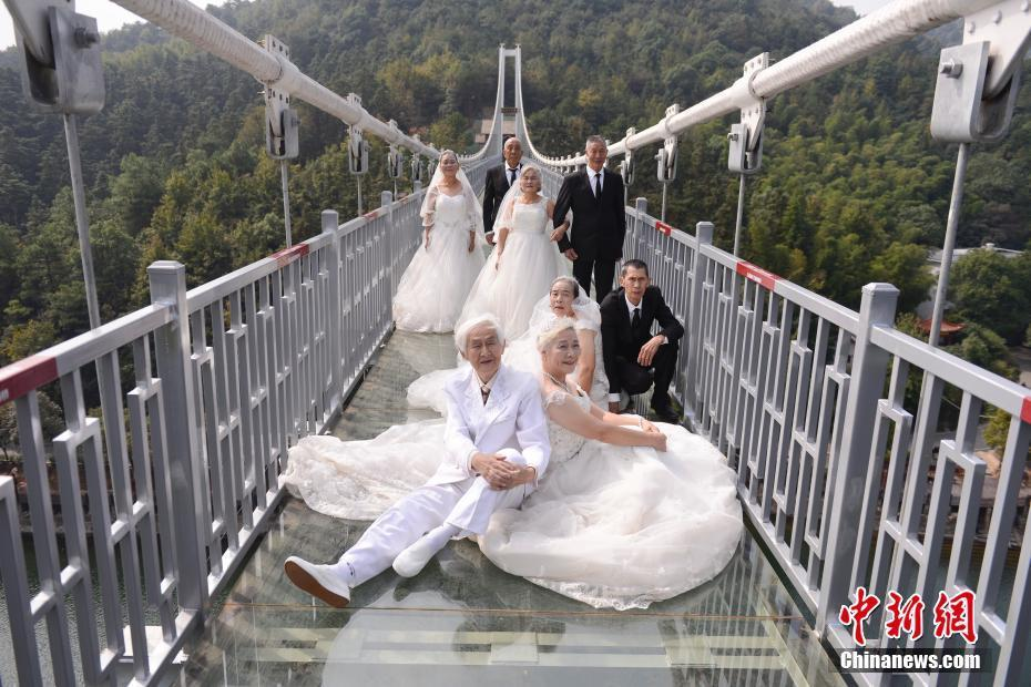 10月26日,四对金婚老人相互搀扶着走上长沙石燕湖跨岛玻璃桥,在垂直近100米的高空拍起了婚纱照,以此特殊的体验庆祝自己的金婚。 杨华峰 摄