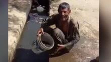印度男子水沟旁洗澡 直接舀出污水淋在身上