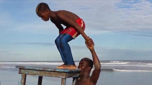 加纳小伙表演牙举桌子火把擦胸杂技
