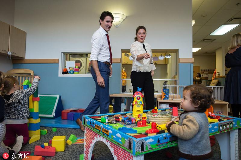 特鲁多偕妻探望儿童 单膝跪地陪小朋友玩耍