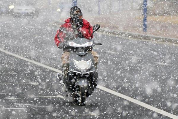 山东烟台迎来今冬首场降雪 市民冒雪出行
