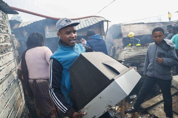南非开普敦一棚屋区发生火灾 居民抱着餐桌电视逃生