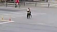 残疾男子横穿马路 辅警背起他一路小跑