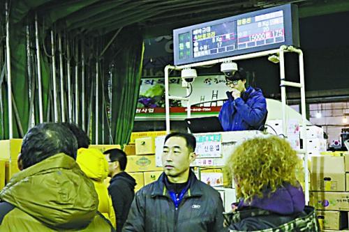 首尔可乐洞,叫卖人在拍卖车上报蔬菜价格。