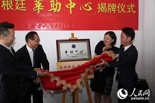 中国侨网国务院侨办副主任郭军(左二)等为华助中心揭牌。人民网记者张卫中摄