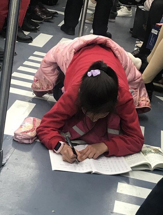 女孩趴地铁上写作业 市民:太不容易