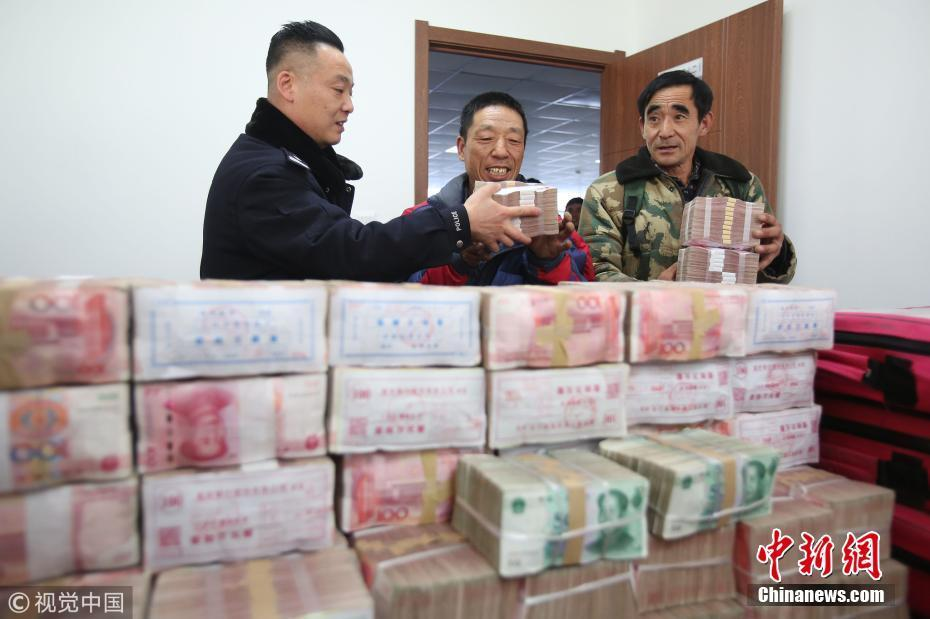 沈阳为农民工发放1400万元欠薪 现金堆满桌