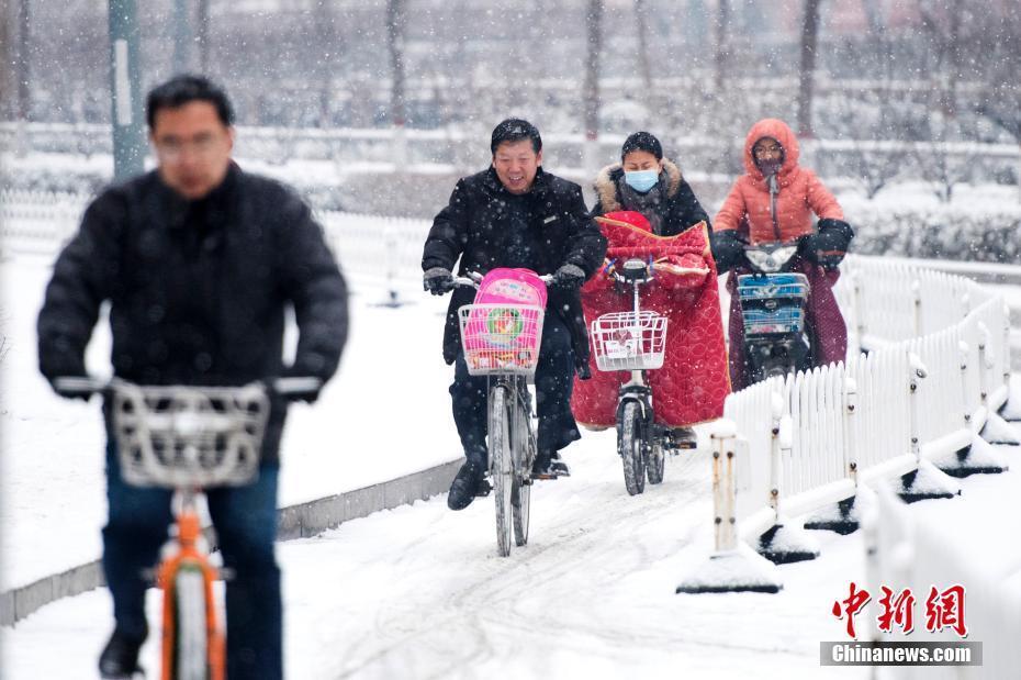 山西迎入冬首场降雪 民众顶雪出行