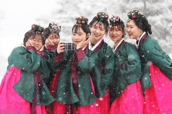 韩国高中毕业生穿传统韩服 雪中合影纪念成年