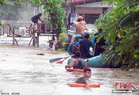 菲律宾卡加廷德奥罗港口城镇遭水淹严重,救援人员用橡皮艇把被困居民从屋子里解救出来。