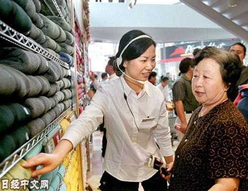 中国侨网资料图片:上海优衣库的店员在为顾客讲解。(图片来源:《日本经济新闻》网站)