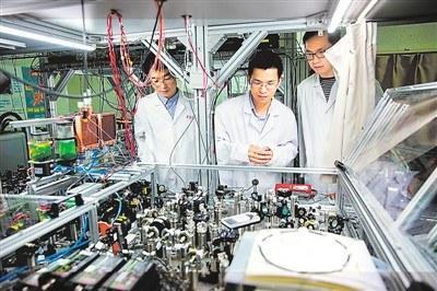 中国侨网2017年5月3日,中国科学技术大学陆朝阳教授(中)和学生们在实验室检查光量子计算机的运行情况。 新华社记者 金立旺摄