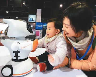 2017年11月23日,在中国义乌国际装备博览会上,一对母子与一台早教型机器人互动。 龚献明摄(人民视觉)